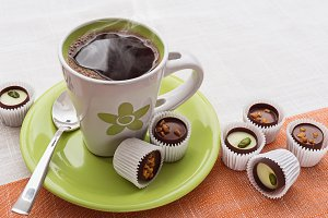 Green cup of coffee and chocolates.