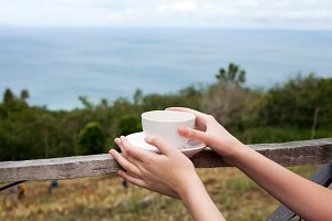 A cup in hands and beautiful seaview