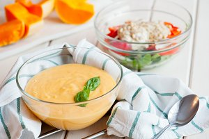 Pumpkin cream soup with basil and pumpkin slice on wooden background