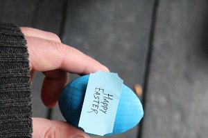 Happy easter. Hand holding an egg with tag. Copy space.