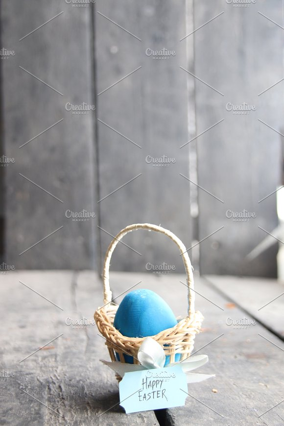 Happy Easter Blue Egg On Rustic Table And A Basket With A Tag