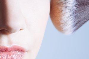 Woman getting powder on her cheek