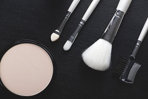 Tools to take care of eyebrows and eyelashes with makeup on black background. Horizontal shoot.