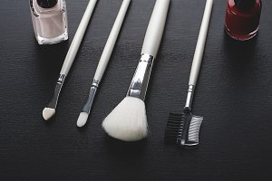 Tools to take care of eyebrows and eyelashes along with red and pink nail makeup. Horizontal shoot.
