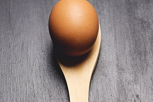 Brown egg on a wooden spoon.