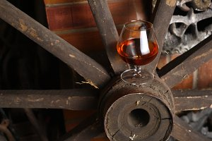 Glass of brandy on wooden wheel