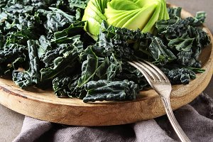 Fresh leaves of Kale salad with avocado, and lemon. Italian Cuisine. Dark background.