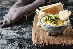 Classic hummus with herbs, olive oil in a vintage ceramic bowl and pita bread. Traditional Middle Eastern cuisine. Dark background.