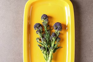 Fresh purple broccoli on a yellow plate. Dark background.