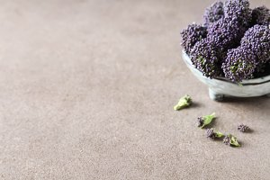 Fresh purple broccoli. Vegan food. Dark background.