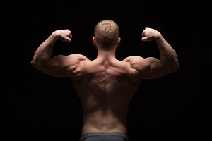Athletic handsome man fitness-model showing his muscular back, isolated on black background with copyspace