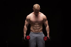 Handsome power man fitness-model with six packs is training with dumbbells, isolated on black background with copyspace