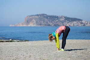 Healthy and fitness lifestyle Young woman stretching on beach in