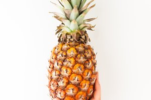 Female hand holding ripe pineapple