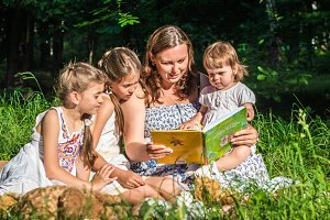 mother reading book with daughters