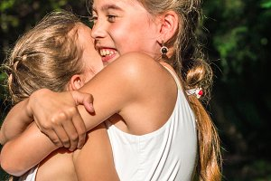 two daughters hugging in the park