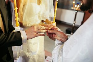 Priest wearing ring on grooms finger