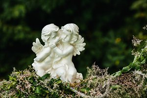 Sculpture of two angels on flowers garland