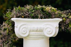 Beautiful flower garland on stone pedestal