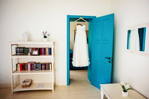Beige wedding dress hangs on peg on door