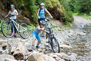 Small boy with his family on bikes wade the stream