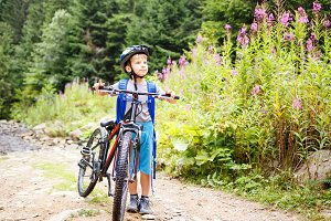 Small boy standing with bicycle on mountain trail