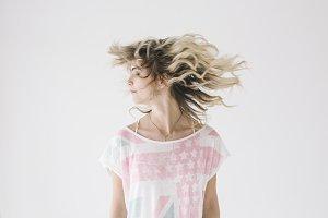 Blonde girl shaking her hair on black background