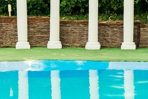 Decorated columns behind turquoise pool