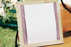 White photo frame on the table for wedding decoration