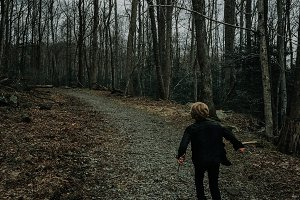 A kid runs on a trail in the woods