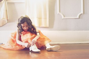 Little Girl Putting on dress shoes