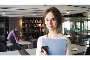 brunet young working woman with blue folder stay with smile in office