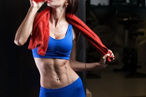 Fitness girl with towel and shaker relaxing in the gym