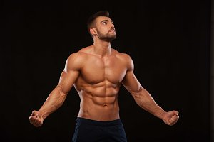 Strong Athletic Man Fitness Model Torso showing six pack abs. isolated on black background with copyspace