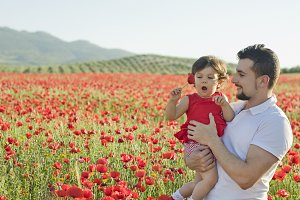 Father and baby in poppies field