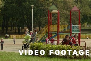 Young mothers with children on playground. Autumn daytime. Smooth dolly shot