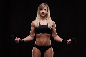 Beautiful athletic woman pumping muscles with dumbbells, isolated on dark background with copyspace