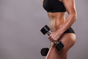 closeup body of fitness woman with dumbbells . Sporty girl showing her well trained body . isolated on grey background with copyspace