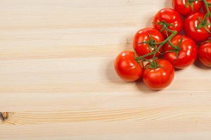 Fresh red tomatoes on the wood table, isolated