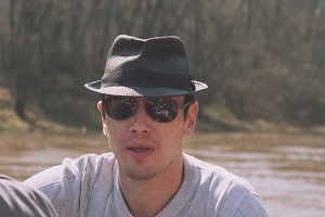 Portrait of Handsome Man in hat and sunglasses near forest river