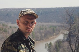 Adult man in military uniform at mount rock river - traveling concept, close up