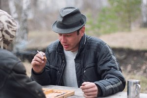 Traveling - young Man in hat in camping smoking and playing backgammon