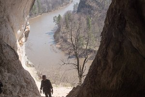 Adult man in military uniform in cave near rock river