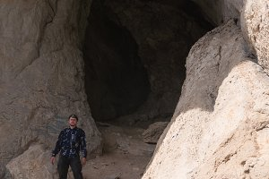 Adult man near mount cave - traveling concept