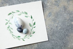 Easter eggs with hand-drawn leaves on paper