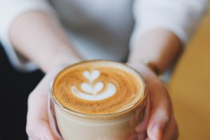 Woman hands holding hot latte coffee