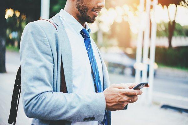 Smiling businessman using smartphon…