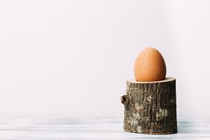 Egg standing on rustic wooden egg cup