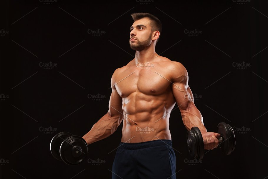 Handsome Athletic Man In Gym Is Pumping Up Muscles With Dumbbells In