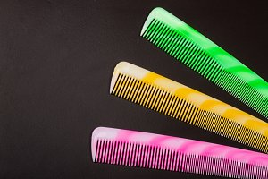 Three different colored hairbrushes on a dark background